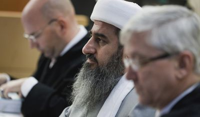 Mullah Krekar (center) sits between his lawyers, Brynjar Meling (left) and Arvid Sjoedin (right), in a courtroom in Oslo on Wednesday, Feb. 15, 2012. The 55-year-old Iraqi-born cleric has pleaded not guilty to charges of making death threats against politicians and encouraging suicide bombings. (AP Photo/Scanpix, Berit Roald)