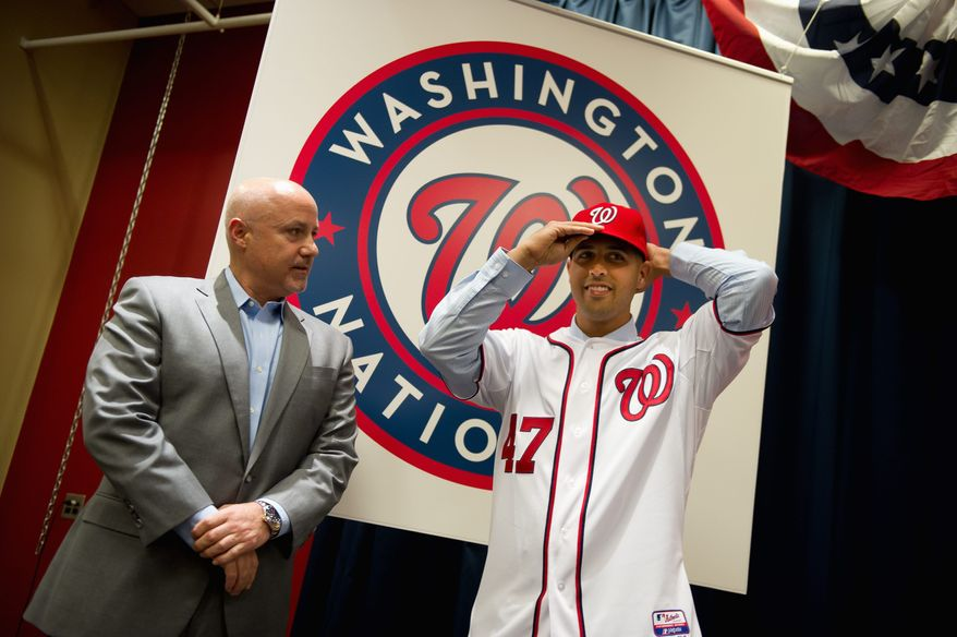 Washington Nationals General Manager and Executive Vice President of baseball operations Mike Rizzo introduces Nationals pitcher Gio Gonzalez, right, who puts on a hat and his jersey at a press conference at Nationals Park, Washington, DC, Wednesday, January 25, 2012. Gonzalez finished last season as a member of the Oakland A's with a 16-12 record, 3.12 ERA and 197 strikeouts in 202 innings pitched. (Andrew Harnik / The Washington Times)