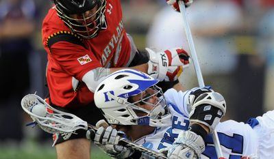Duke's Zach Howell looks to pass after falling to the ground as Maryland's Jesse Bernhardt tries to take the ball in an NCAA Division I Lacrosse semi final game Saturday, May 28, 2011 in Baltimore.(AP Photo/Gail Burton)