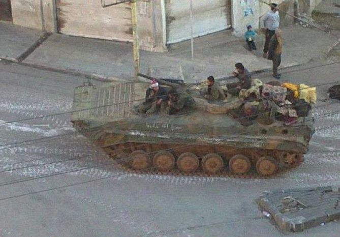 "Government army soldiers on top of an armored personnel carrier patrol a street at the mountain resort town of Zabadani, Syria, near the Lebanese border. A human rights group said Syrian troops ""committed a new massacre"" near the northwestern town of Jisr al-Shughour, killing 19 people - 11 of them from the same family. The report was impossible to confirm."