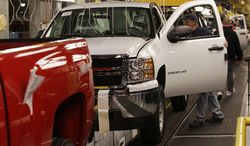 Heavy-duty pickups are assembled in a General Motors' plant in Flint, Mich. The company announced Thursday that it made a record profit of $7.6 billion in 2011as it reclaimed the title of world's largest automaker. (Associated Press)