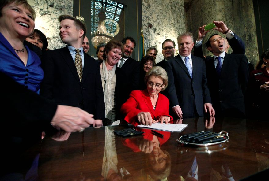 Washington state Gov. Chris Gregoire is surrounded by legislators and others Monday as she signs into law a bill legalizing same-sex marriage. The law is to take effect June 7, but opponents are mounting a repeal effort. (Associated Press)