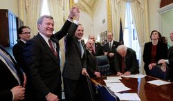 Senate Finance Committee Chairman Max Baucus (left) and House Ways and Means Committee Chairman Dave Camp raise their hands Thursday on Capitol Hill. Congressional leaders gathered to sign off on a final deal to extend the payroll-tax cuts through the rest of this year. (Associated Press)