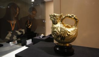 A gold pot is displayed for sale Feb. 16, 2012, in a booth from China at the International Jewelry Fair in Hong Kong. (Associated Press)