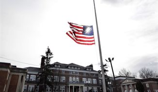 An American flag flies at half-staff in front of the Whitney E. Houston Academy of Creative and Performing Arts in East Orange, N.J., on Feb. 12, 2012. (Associated Press)