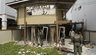 **FILE** Thai Explosive Ordnance Disposal (EOD) officials examine Feb. 15, 2012, the damage caused by a blast at the house where suspected bomber Saeid Moradi was staying in Bangkok. Two Iranian suspects arrested in Bangkok after three explosions hit the city were likely planning to attack individuals but did not have the capacity to target large crowds or buildings, Thai police said. (Associated Press)