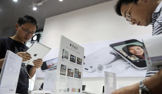 **FILE** Customers try out iPad tablet computers May 6, 2011, at an Apple's authorized dealer outlet in Changsha in south China's Hunan province. (Associated Press)
