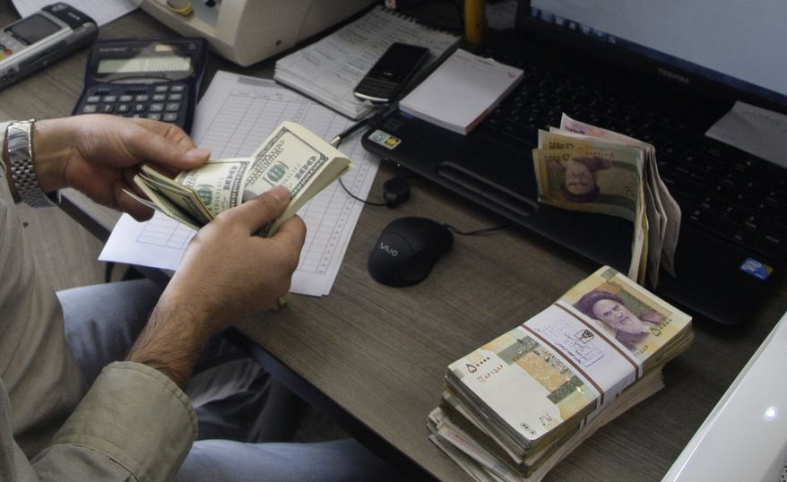 **FILE** A currency exchange bureau worker counts U.S. dollars, as Iranian bank notes are seen at right with portrait of late revolutionary founder Ayatollah Khomeini, in downtown Tehran on Dec. 21, 2011. (Associated Press)