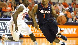 Virginia's Jontel Evans drives past Clemson's Andre Young during the first half Tuesday, Feb. 14, 2012, in Clemson, S.C. Clemson won 60-48. (AP Photo/Rainier Ehrhardt)