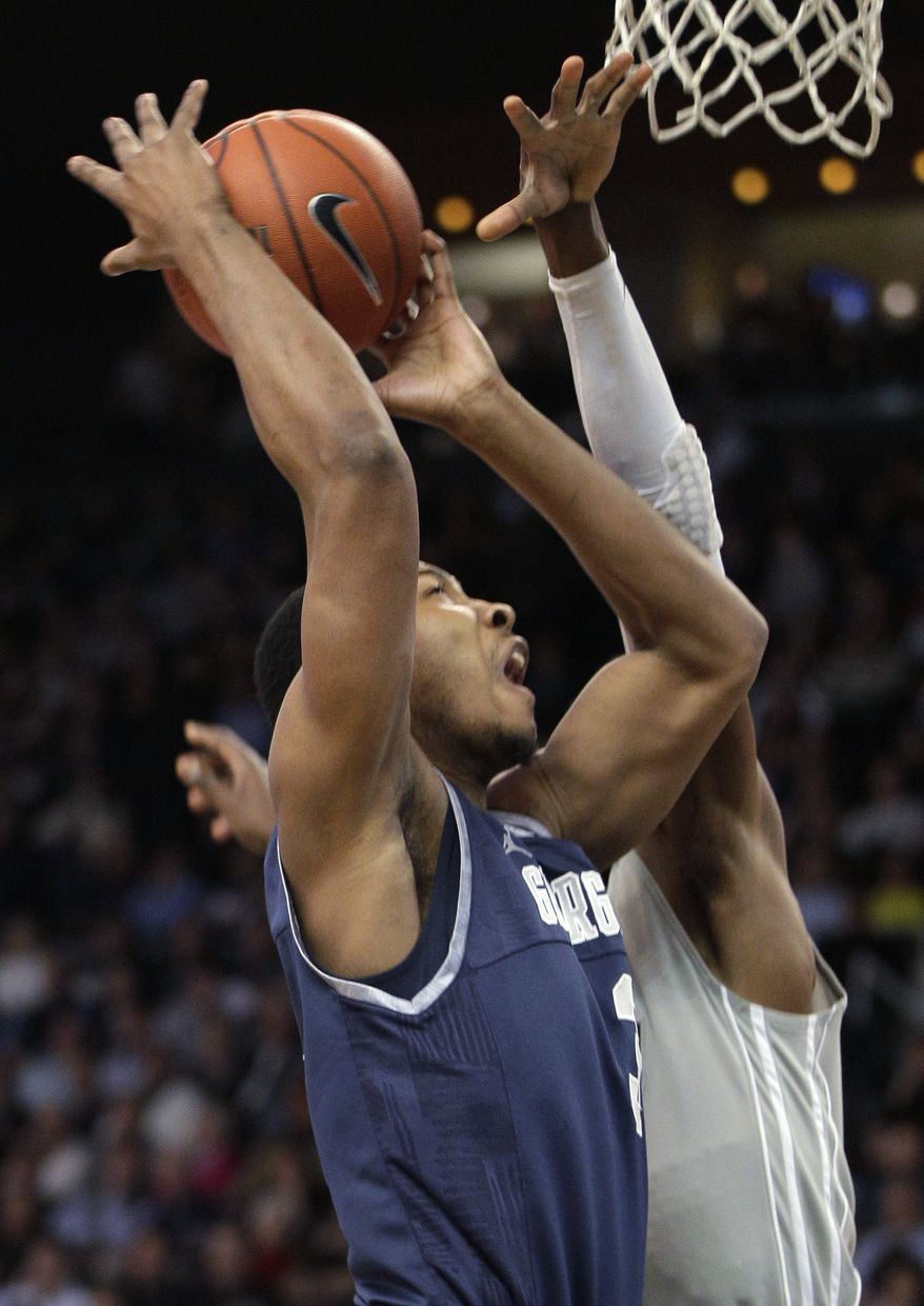 Georgetown forward Mikael Hopkins takes the ball to the basket against Providence forward Brice Kofane during the first half in Providence, R.I., Saturday, Feb. 18, 2012. (AP Photo/Stephan Savoia)