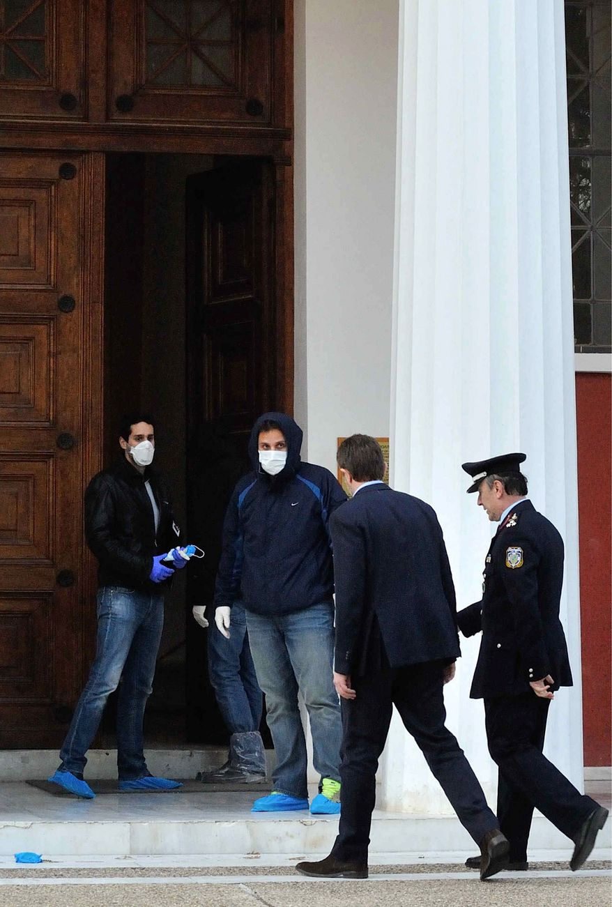 Police forensic experts, left, look on as Greece's Culture Minister Pavlos Geroulanos, second right, enters the antiquities museum in Ancient Olympia where two masked armed robbers tied up a guard and made off with dozens of artifacts, Olympia, southern Greece, Friday, Feb. 17, 2012. Friday's robbery is the second major museum theft in the past two months in Greece. In January, thieves made off with art works by 20th century masters Pablo Picasso and Piet Mondrian from the country's National Gallery in central Athens. Geroulanos has submitted his resignation after the robbery. (AP Photo/Dimitris Papaioannou)