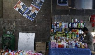 A shopkeeper waits for customers in Sanaa on Thursday as campaign posters showing Yemeni Vice President Abed Rabbo Mansour Hadi hang on the wall. President Obama backed the vice president days before the election. Mr. Hadi is the only candidate. (Associated Press)