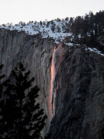 The firefall  from Glacier Point in Yosemite National Park presents itself as a molten lava flow at sunset in mid-February when the sun and Earth align to create a fleeting phenomenon and winter weather cooperates. (National Park Service via Associated Press)