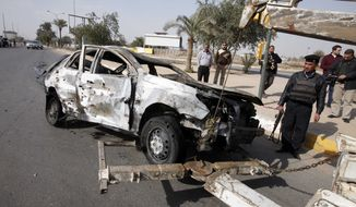 Security forces prepare to tow away a destroyed automobile after a car bombing outside the fortified police academy near the Interior Ministry headquarters in Baghdad on Sunday, Feb. 19, 2012. (AP Photo/Karim Kadim)