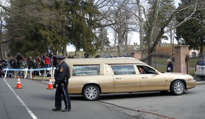 The hearse carrying the body of singer Whitney Houston arrives at Fairview Cemetery in Westfield, N.J., for her burial on Sunday, Feb. 19, 2012. (AP Photo/Rich Schultz)