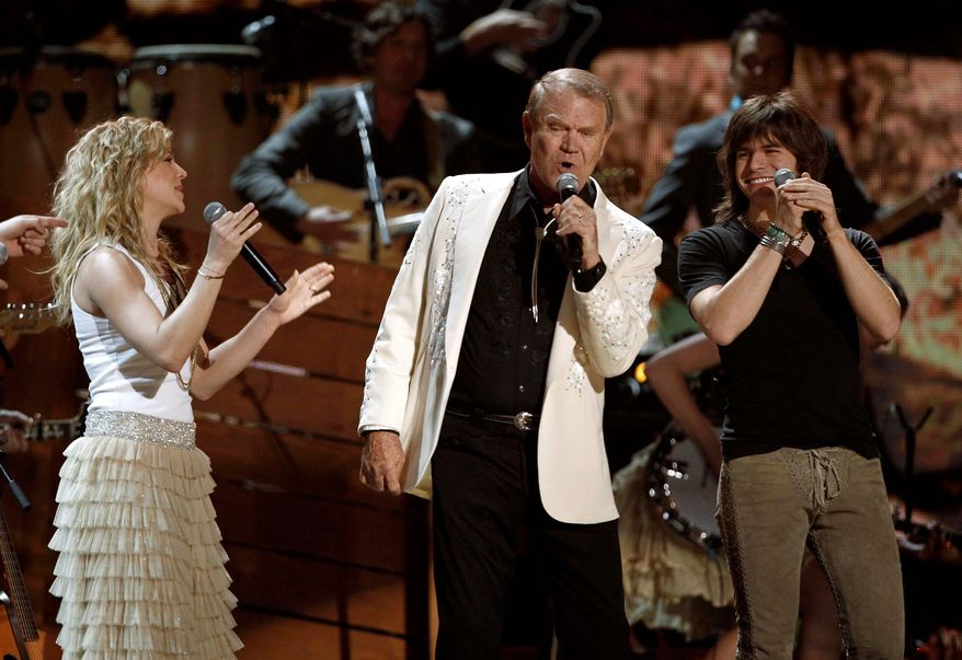 Kimberly Perry and Reid Perry, two-thirds of the country music trio Band Perry, flank Glen Campbell as he performs at the Grammy Awards on Feb. 12 in Los Angeles. Mr. Campbell's Alzheimer's disease was not in evidence during his performance. (Associated Press)