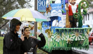 Carnival revelers wave to passing floats near the start of the Krewe of Endymion parade, which was postponed for an hour because of heavy rain, in New Orleans on Saturday, Feb. 18, 2012. (AP Photo/Jonathan Bachman)
