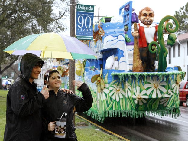Carnival revelers wave to passing floats near the start of the Krewe of Endymion parade, which was postponed for an hour because of heavy rain, in New Orleans on
