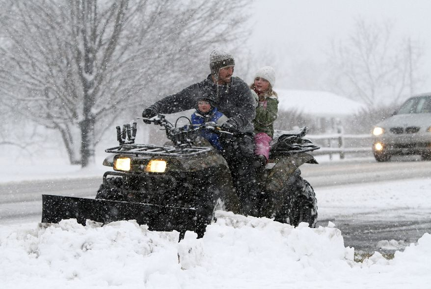 Chad Ellinger and his son Trip, 2, and daughter Morgan, 6, push snow from their driveway in Augusta County, Va., on Sunday Feb. 19, 2012. (AP Photo/Norm Shafer)