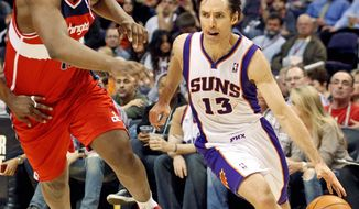 Phoenix Suns guard Steve Nash, right, drives past Washington Wizards forward Kevin Seraphin on his way to the basket in the third quarter of an NBA basketball game Monday, Feb. 20, 2012, in Phoenix. The Suns won 104-88. (AP Photo/Paul Connors)