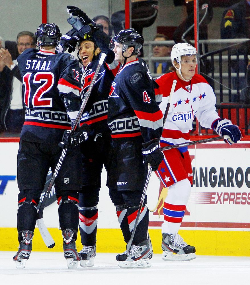 Carolina Hurricanes' Anthony Stewart, center left, is congratulated on his goal by teammates Eric Staal (12) and Jamie McBain (4) as Washington Capitals' Alexander Semin (28), of Russia, skates by during the first period of an NHL hockey game in Raleigh, N.C., Monday, Feb. 20, 2012. The Hurricanes won 5-0. (AP Photo/Karl B DeBlaker)
