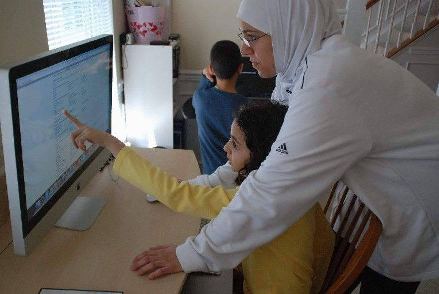 """Sarah Yazback helps her daughter Zainab find an arithmetic lecture video online. """"I am here for resources and help if necessary,"""" Ms. Yazback says, """"but the kids are very independent and self-guided with their lessons."""" (Jessica Carpenter/The Washington Times)"""