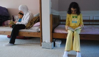 PHOTOGRAPHS BY JESSICA CARPENTER/THE WASHINGTON TIMES SCHOOL DAYS: Sarah Yazback reads a book to her son Musa Bannout, 3, while her daughter Zainab Bannout, 9, reads on her own in the family's Germantown home. Ms. Yazback said she allows the children to choose what to read and what to learn, and they spend all day with activities and lessons that help stimulate their brains.