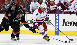Washington Capitals' Alex Ovechkin has the puck poked away by Carolina Hurricanes' Brandon Sutter (16) with Hurricanes' Tim Gleason nearby, during the first period in Raleigh, N.C., Monday, Feb. 20, 2012. (AP Photo/Karl B DeBlaker)