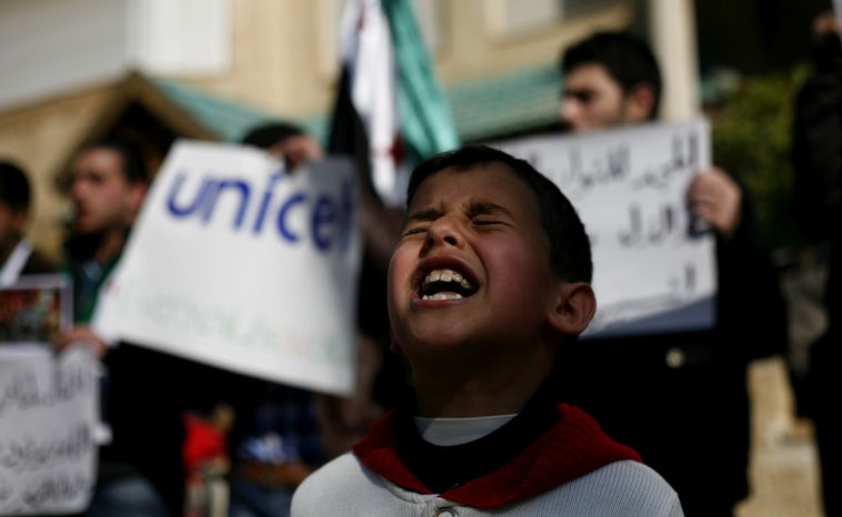 A Syrian boy chants slogans Feb. 20, 2012, during a rally demanding UNICEF to protect Syrian children in front of the UNICEF Compound in Amman, Jordan. (Associated Press)