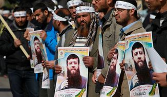 Palestinian supporters of Khader Adnan, a senior member of the Islamic Jihad who has been on a hunger strike for 66 days while being jailed in Israel, demonstrate in Gaza City, Gaza Strip, on Tuesday, Feb. 21, 2012. (AP Photo/Hatem Moussa)