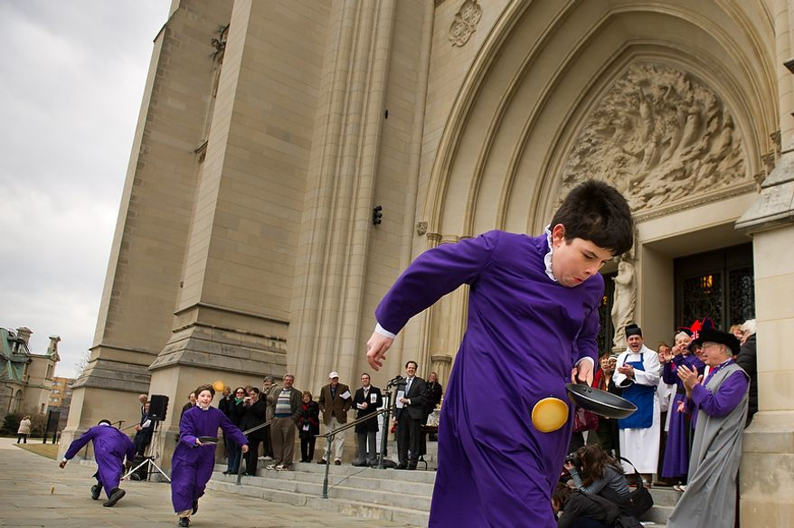 "Left to right: Seventh grader Guyton Harvey and eighth grader Justin Frazier struggle to keep up as six grader Zachary Martin, right, wins the St. Albans School Boy Chorister race during the Washington National Cathedral Pancake Races held in front of the Cathedral on Shrove Tuesday, more commonly known as ""Mardi Gras."", Washington, D.C., Tuesday, Feb. 21, 2012. This years annual Pancake Races are entitled the ""Shake, Rattle & Race Edition,†in light of the earthquake damage the cathedral sustained earlier this year. (Andrew Harnik/The Washington Times)"