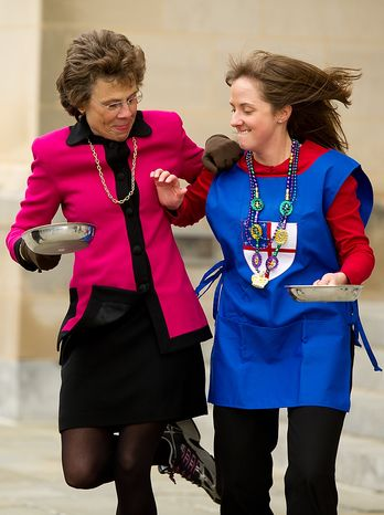 """Suzy Mink, senior advisor of institutional relations anddevelopment, left and Haley Dettra, events and special services manager Washington National Cathedral jokingly fight for a better starting position during the Pancake Races held in front of the Cathedral on Shrove Tuesday, more commonly known as """"Mardi Gras."""", Washington, D.C., Tuesday, Feb. 21, 2012. This years annual Pancake Races are entitled the """"Shake, Rattle & Race Edition,†in light of the earthquake damage the cathedral sustained earlier this year. (Andrew Harnik/The Washington Times)"""