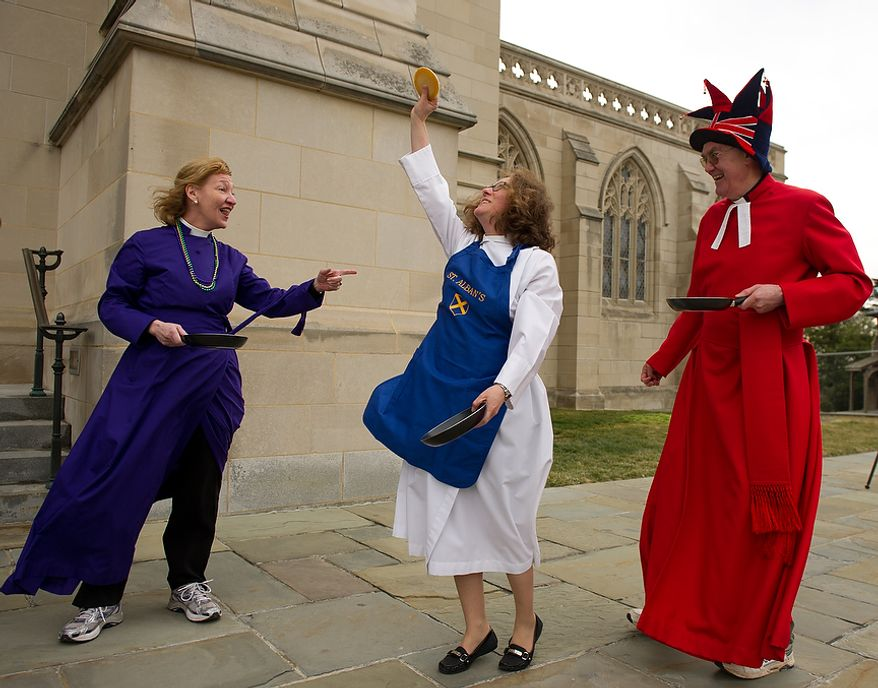 "Rev. Deborah Meister, Rector of St. Alban's Parish holds her pancake triumphantly over her head after winning her race against the Rev. Canon Jan Naylor Cope, National Cathedral Vicar, left, and the Rev. Canon Ralph Godsall, priest vicar of Westminster Abbey and visiting clergy at the National Cathedral during the Washington National Cathedral Pancake Races held in front of the Cathedral on Shrove Tuesday, more commonly known as ""Mardi Gras."", Washington, D.C., Tuesday, Feb. 21, 2012. This years annual Pancake Races are entitled the ""Shake, Rattle & Race Edition,†in light of the earthquake damage the cathedral sustained earlier this year. (Andrew Harnik/The Washington Times)"