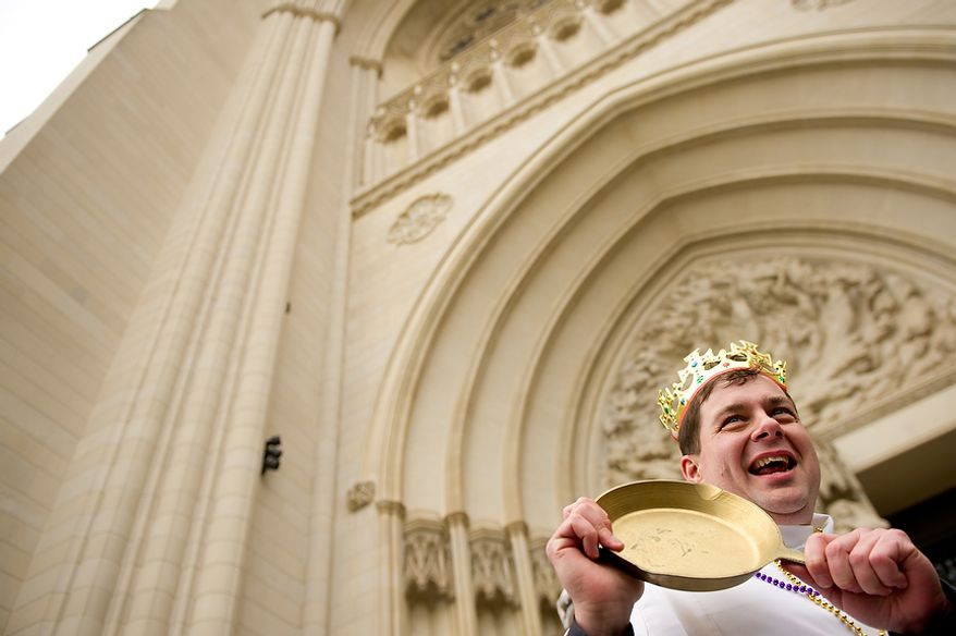 """Assistant Rector for St. Alban's Parish Reverend Matthew Hanisian proudly shows off his """"golden skillet"""" after winning the final champion's race at the Washington National Cathedral Pancake Races held in front of the Cathedral on Shrove Tuesday, more commonly known as """"Mardi Gras."""", Washington, D.C., Tuesday, Feb. 21, 2012. This years annual Pancake Races are entitled the """"Shake, Rattle & Race Edition,†in light of the earthquake damage the cathedral sustained earlier this year. (Andrew Harnik/The Washington Times)"""