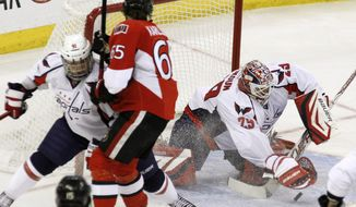 Washington Capitals goaltender Tomas Vokoun plays the puck as Ottawa Senators' Erik Karlsson, center, works against Capitals' Dmitry Orlov during the first period in Ottawa, Ontario, on Wednesday, Feb. 22, 2012. (AP Photo/The Canadian Press, Fred Chartrand)