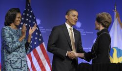 President Obama and former first lady Laura Bush (right) shake hands as first lady Michelle Obama looks on during the groundbreaking ceremony for the Smithsonian Institution's National Museum of African American History and Culture in Washington on Wednesday, Feb. 22, 2012. (AP Photo/Susan Walsh)