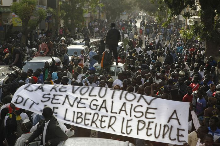 "Anti-government protesters carry a banner reading ""The Senegalese revolution said to liberate the people,"" as they are blocked by police from reaching Independence Square in central Dakar, Senegal, on"