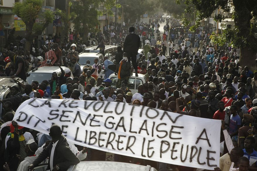 """Anti-government protesters carry a banner reading """"The Senegalese revolution said to liberate the people,"""" as they are blocked by police from reaching Independence Square in central Dakar, Senegal, on Feb. 21, 2012. (Associated Press)"""