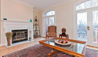 The living room has a wood-burning fireplace. Two sets of glass doors with arched transoms lead to the enclosed backyard.