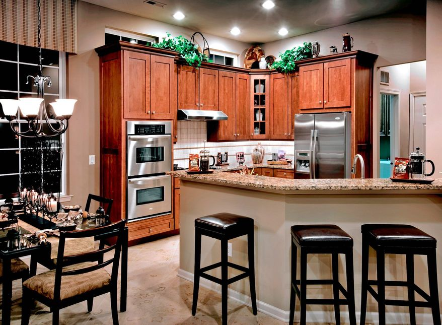 The kitchen has 42-inch cabinets, granite counters, a tile backsplash and a breakfast bar.