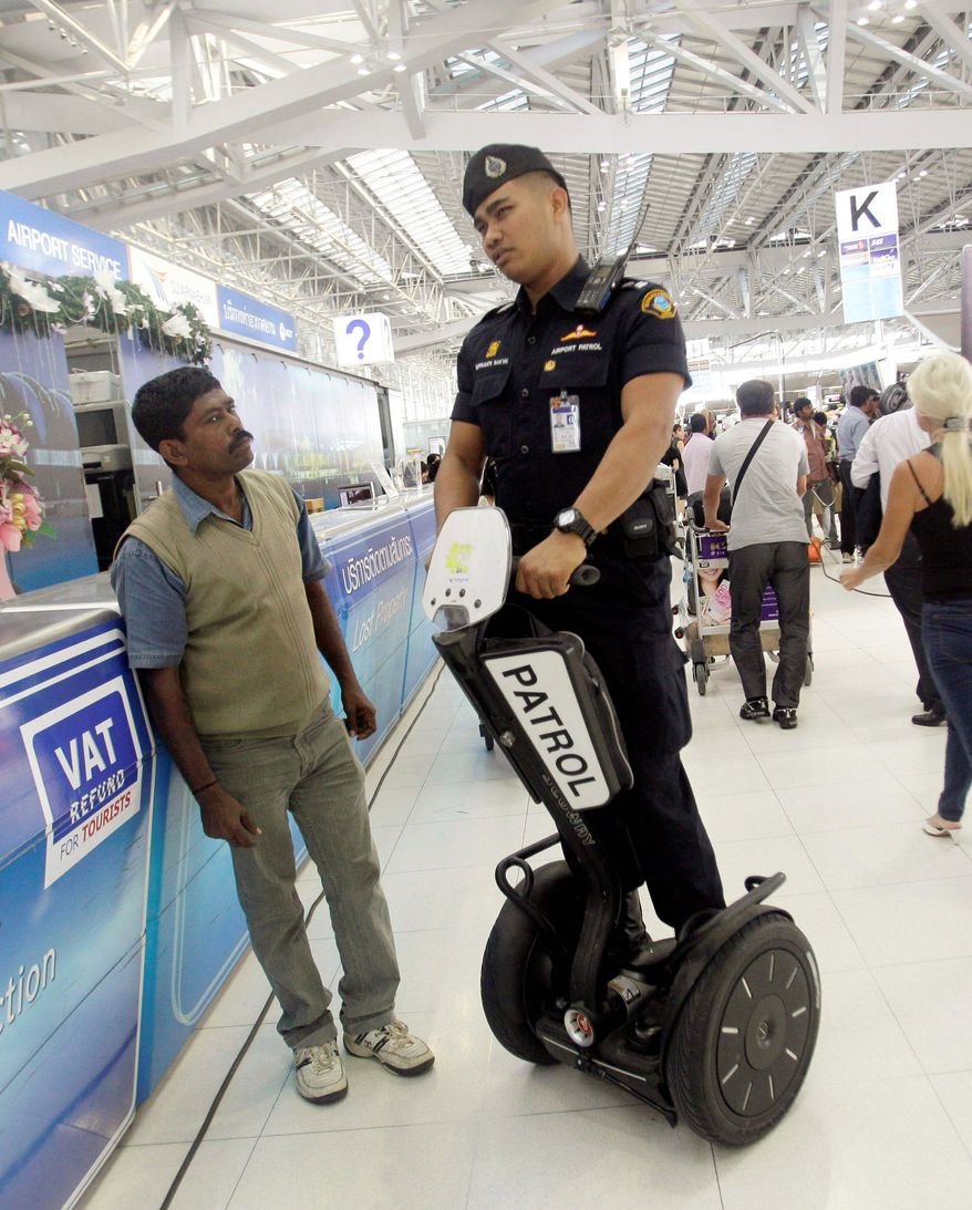 An airport security officer talks to a tourist during a patrol at Bangkok International Suvarnabhumi Airport on Feb. 17, three days after one of the suspects in a botched Valentine's Day terrorism plot flew back to Tehran. (Associated Press)