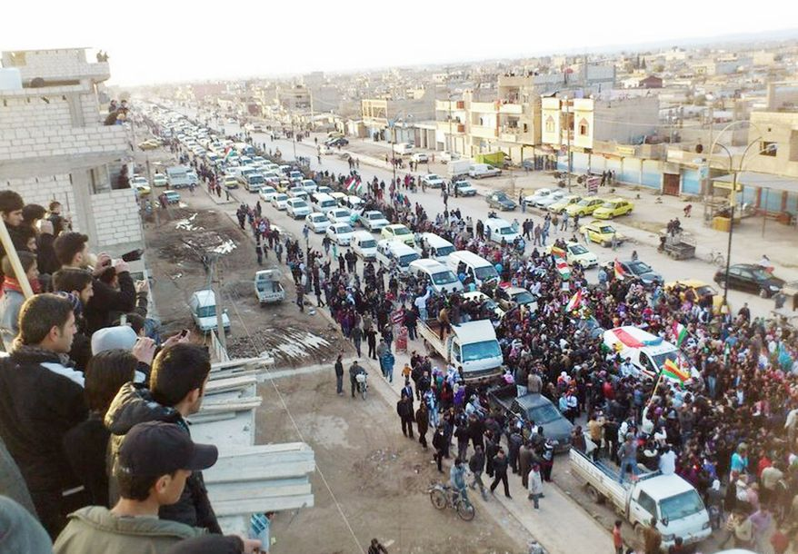 Opponents of the Syrian regime of President Bashar Assad hold up Kurdish flags Wednesday at a rally in Qamishli, Syria, in an image provided by activists, the authenticity of which could not be independently verified. (Associated Press)