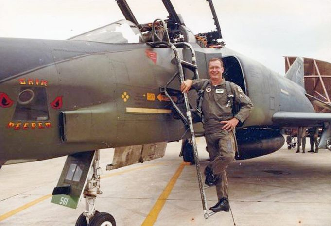 Air Force Lt. Col. Mike Ross stands beside a reconnaissance aircraft similar to the one he was flying in a 1987 training mission when he was shot down by a Navy pilot and had to eject.