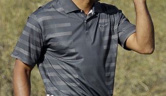 Tiger Woods removes his cap after missing a putt on No. 18 to lose the match 1-up to Nick Watney during the second round of the Match Play Championship golf tournament, Thursday, Feb. 23, 2012, in Marana, Ariz. (AP Photo/Eric Risberg)
