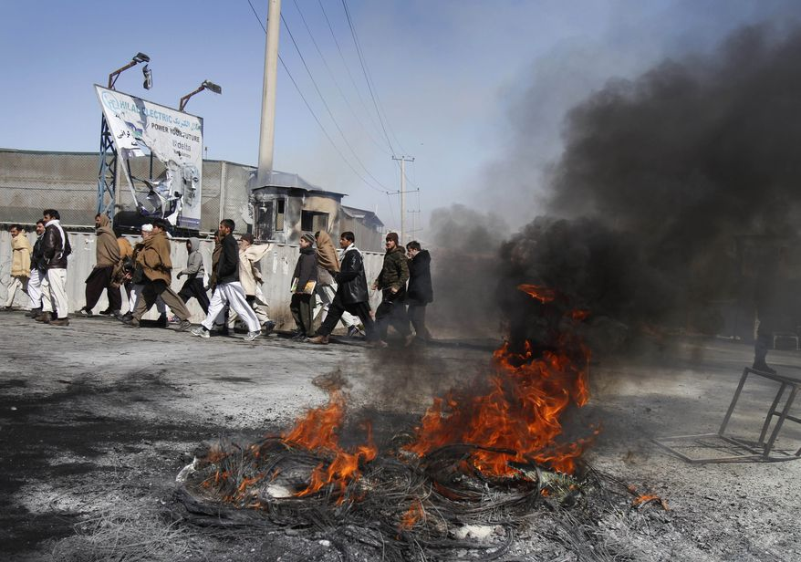 Afghans walk past tires that were burnt by protesters during an anti-U.S. demonstration in Kabul, Afghanistan, on Feb. 22, 2012. (Associated Press)