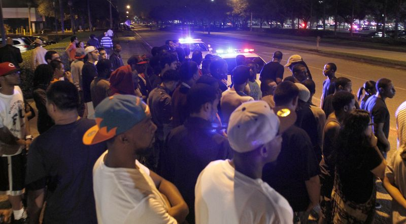 Police hold back crowds near the Florida Mall in Orlando, Fla., late Feb. 23, 2012, after more than 100 sheriff's deputies in riot gear broke up an out-of-control crowd waiting to buy a new Nike basketball shoe at one of the stores. (Associated Press)