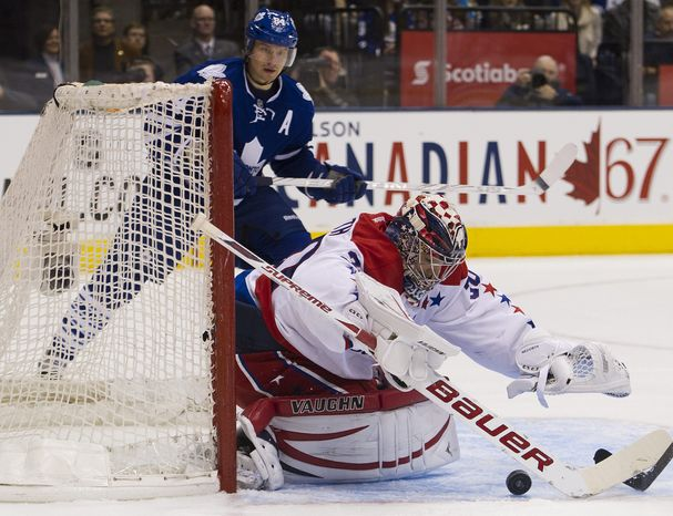 Washington Capitals goalie Michal Neuvirth covers a loose puck as Toronto Maple Leafs' Mikhail Grabovski, looks on during second-period action in Toronto, Saturday, Feb. 25, 2012. Neuvirth made 28 saves in the 4-2 win. (AP Photo/The Canadian Press, Nathan Denette)