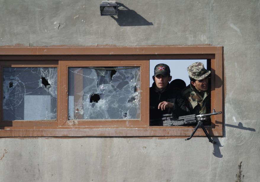 Afghan soldiers watch the protestors from the window of a guard tower during an anti-U.S. demonstration in Kabul, Afghanistan, Friday, Feb. 24, 2012. Thousands of Afghans staged new demonstrations Friday over the burning of Korans at a U.S. military base in Afghanistan. (AP Photo/Ahmad Jamshid)