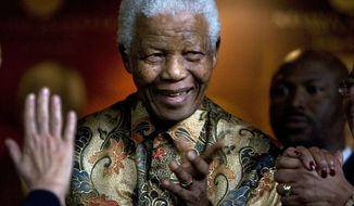 ** FILE ** Former South African President Nelson Mandela smiles as German Chancellor Angela Merkel (left) waves farewell after a meeting at the Nelson Mandela Foundation in Johannesburg in October 2007. (AP Photo/Peter Dejong, File)