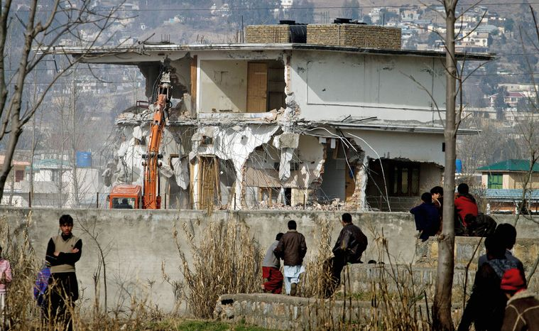Local residents watch as authorities use heavy machinery to demolish the compound of Osama bin Laden in Abbottabad, Pakistan, on Sunday, Feb. 26, 2012. (Associated Press) ** FILE **